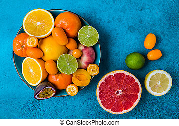Summer and citrus fruits in bowl on blue background