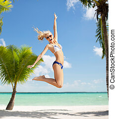 laughing woman jumping on the beach