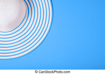 Summer and vacation concept. Top view of straw striped hat on blue color background. Flat lay.