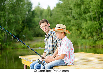 Father and son sitting on bridge and fishing
