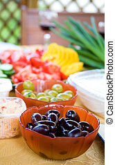 Summer appetizers. Black and green olives and sliced fresh vegetables on a table. Shallow depth of field, focus on black olives