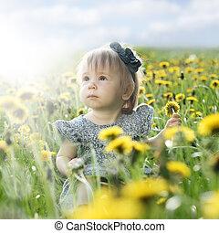 Summer baby girl on green grass outdoors