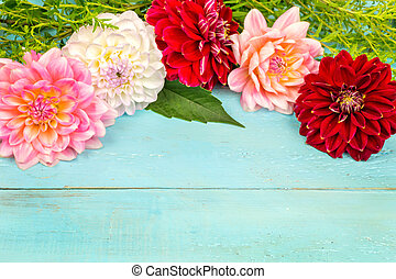summer background. dahlias and a canvas on a blue wooden background. art. space for a text