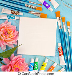 summer background. dahlias, paints, brushes and a canvas on a blue wooden background. art. space for a text