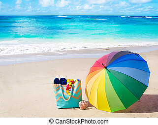 Summer background with rainbow umbrella and bag on the sandy beach