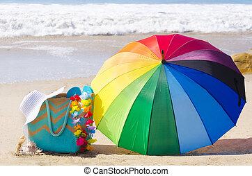 Summer background with rainbow umbrella and beach bag