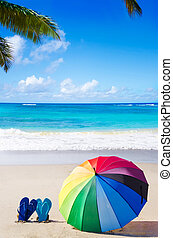 Summer background with rainbow umbrella and flip flops