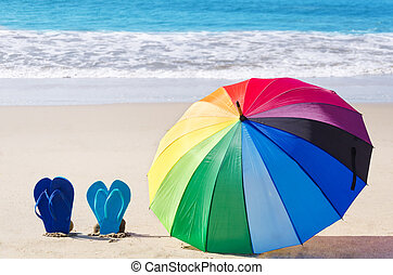 Summer background with rainbow umbrella and flip flops