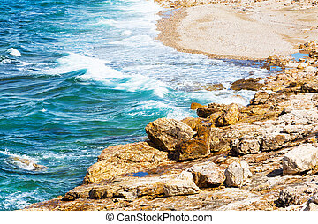 Summer background with waves on stone beach shore