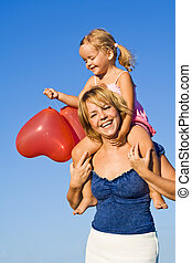 Woman and little girl having some balloon fun outdoors in summer time