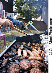 summer bbq in a garden with sausages and burgers