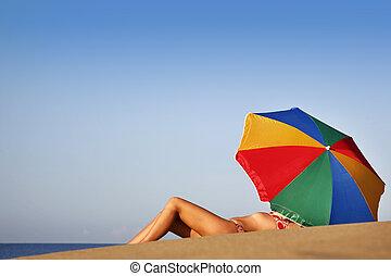 Summer Beach Babe - Pretty woman under parasol on the beach