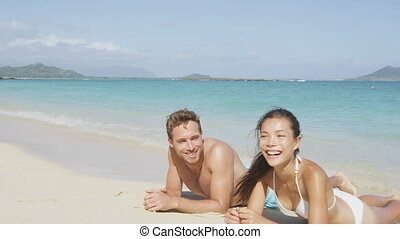 Summer beach couple on honeymoon relaxing happy laughing and smiling having fun lying down in sand. Woman and man enjoying sun tanning and summer sun on pristine paradise beach.