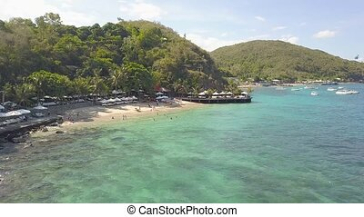 Summer beach resort and blue sea water aerial landscape. People resting on beach and swimming in sea bay. Drone view sandy beach on tropical island and green hill landscape.