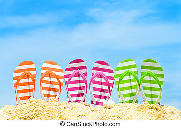 Summer beach - Row of multicolor flip flops on beach against...