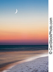 Summer beach scene just after sunset with crescent moon in long exposure image
