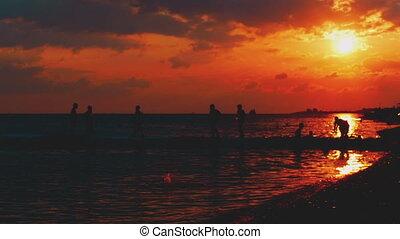 Summer beach vacation at sunset, children running around the dancing bridge, playing catch-up at sunset.
