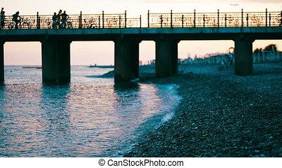 Summer beach vacation at sunset, the bridge is over the bridge, the airplane is flying at sunset.