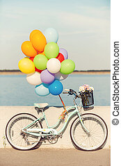Summer bike. Picture of vintage bicycle with balloons and flowers in basket