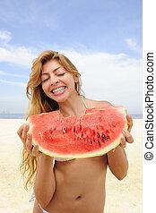 woman eating watermelon on the beach