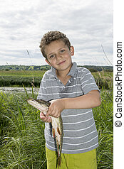 Summer boy stands near the lake and holding a big pike.