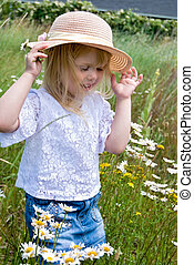 Summer Breeze - Little girl hanging on to her summer hat in...