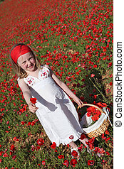 summer child picking flowers in meadow of poppies