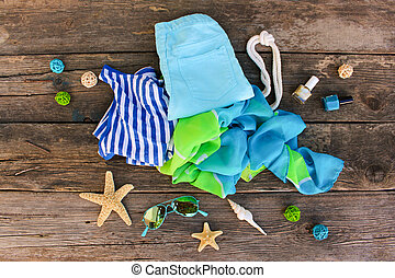 Summer clothes and accessories on old wooden background. Top view, flat lay.
