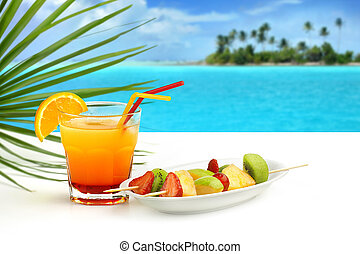 summer cocktail and fruit skewers on exotic seascape