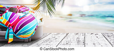 Summer concept of colorful bikini and clothes in luggage on the wooden floor at beach