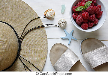 summer concept- raspberries, straw hat, slippers and shells on white wooden background