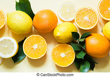 Summer concept. Set of tropical fruits, lemon, orange and green leaves on yellow. Close up. Top view.
