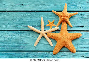 Starfish on blue wooden background. Top view .