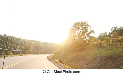 Summer country drive into sun.
