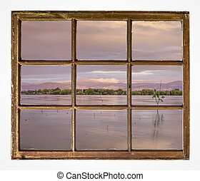 summer dawn over calm lake - window view