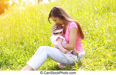 Summer day, happy mother and child outdoors on the grass