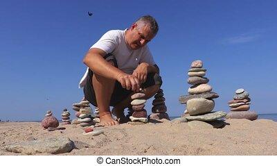 Summer day man builds balanced stone pyramid on the beach...