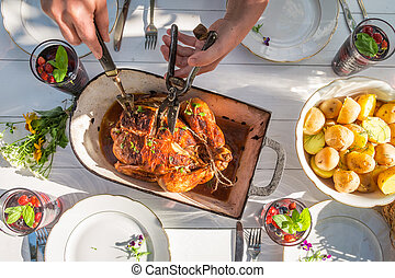 Summer dinner with chicken and potatoes served in the garden