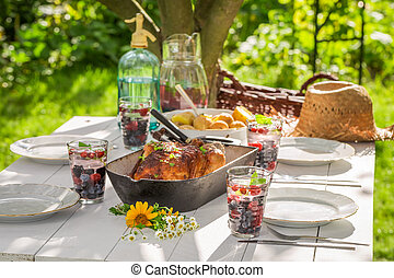 Summer dinner with potatoes and chicken served in the garden