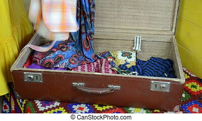 hands finishes packing a suitcase folding summer dress in a suitcase