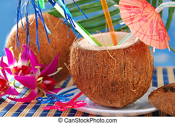 summer fruit drink served in coconut shell on the beach