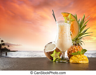 Exotic summer drink served on stone. Blur beach as background