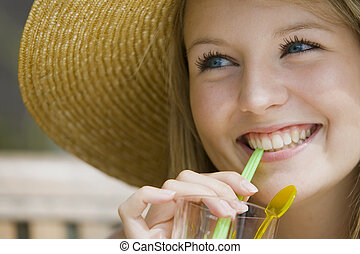 Summer Drinks - A beautiful young blond woman enjoying a...