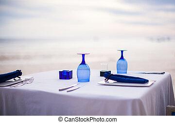 Summer empty open air table set for dinner on white beach