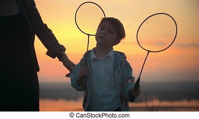 Summer evenin grandson and grandmother at scarley sunset .The grandmother adjusts her clothes and leaves a grandson. Grandson holds a badminton racket and dreams