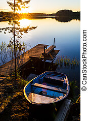summer evening landscape with a boat at the pier on a lake