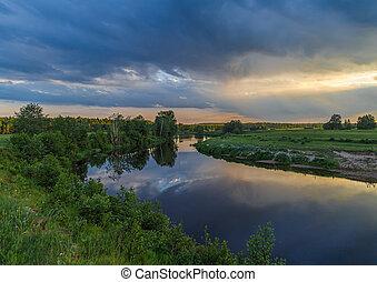 Summer evening, the river flows through a field