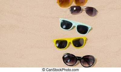 various sunglasses on beach sand