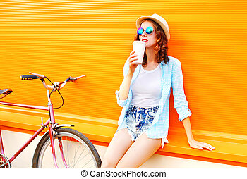 Summer fashion woman drinks coffee from cup with bicycle on a colorful orange background