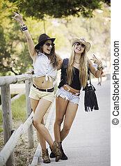 summer fashion young women in shorts and sun hats.
